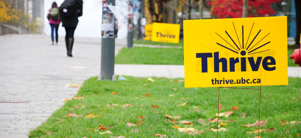 A yellow thrive event lawn sign on University Boulevard