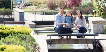 A family looks at a fountain in Wesbrook Place
