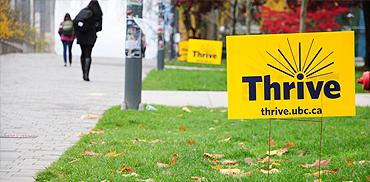 A photo of a yellow Thrive event lawn sign on University Boulevard